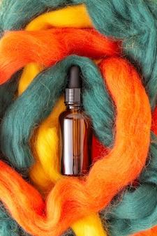 カラフルなウールの糸にピペットが付いた茶色のガラス瓶