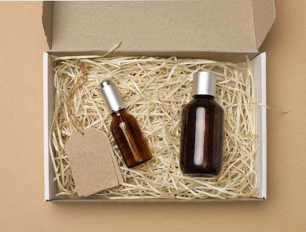 化粧品用の茶色のガラス瓶とロープ上の紙のタグは、ベージュの背景、上面図の段ボール紙箱にあります