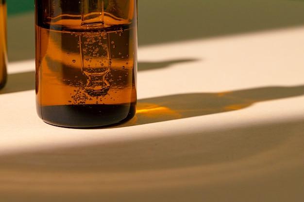 油性スキンケア美容液と茶色のガラス瓶が白いテーブルにクローズアップ