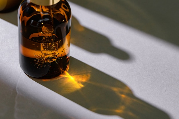 Brown glass bottles with oily skincare serum close up on white table