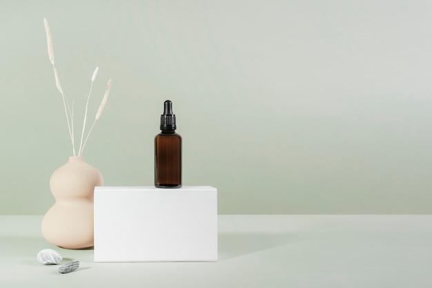 흰색 상자 제품 모형이 있는 갈색 유리 스포이드 병