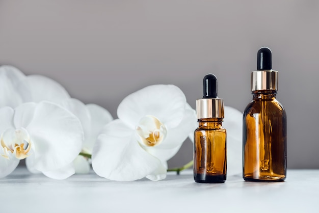 Brown glass serum or essential oil bottles mockup with orchid flowers in the background, natural skin care and beauty cosmetic skin products, home spa in a dropper bottle
