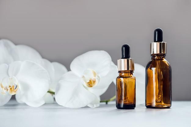 갈색 유리 세럼 또는 에센셜 오일 병은 배경에 난초 꽃, 천연 피부 관리 및 미용 화장품 피부 제품, 스포이드 병에 담긴 홈 스파
