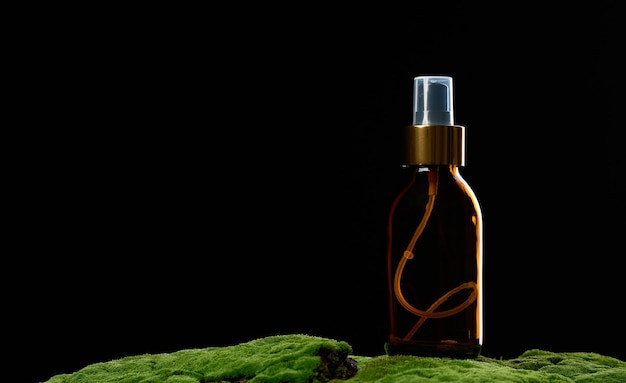 緑の苔の上に茶色のガラスのスプレーボトルが立っています。化粧品spaブランド。パッケージング、広告、製品プロモーション、モックアップ