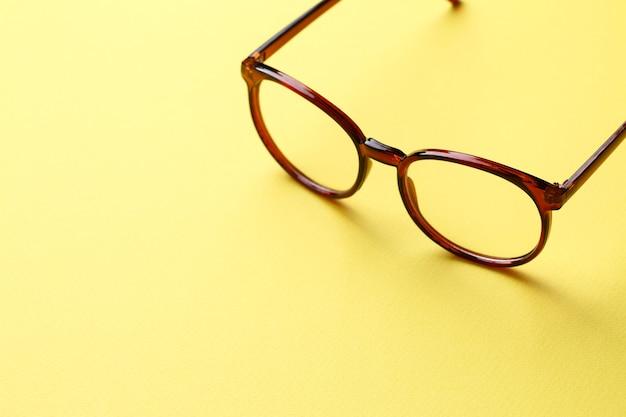 黄色の背景に茶色のメガネ