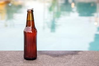 Brown grass bottle of liquid on rim of swimming pool