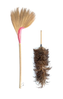 Brown grass broom and feather duster isolated on white background