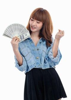 彼女の手に広がり、興奮した拳を上げるアメリカの紙幣を持っている茶色の髪のアジアの女性、白い背景で撮影されたスタジオ。
