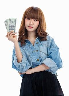 手に広がるアメリカの紙幣を持っている茶髪のアジア人女性、彼女はそれを使用する方法を考え、白い背景でスタジオ撮影しました。