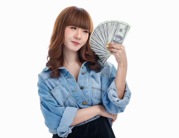 彼女の手に広がるアメリカの紙幣を持って幸せを感じる茶色の髪のアジアの女性、彼女は笑顔で、白い背景でスタジオ撮影。