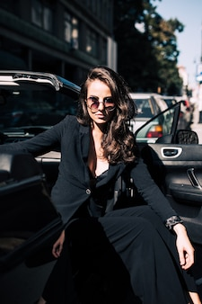 Brown hair sexy woman on the seat of the car