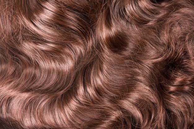 갈색 머리 짜임새. 물결 모양의 긴 곱슬 밝은 갈색 머리를 배경으로 닫습니다. 헤어 익스텐션, 재료 및 화장품, 헤어 케어. 헤어 스타일, 이발 또는 살롱에서 죽어가는 것.