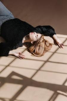 黒のふわふわセーターの茶色の髪の女性