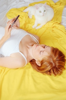 茶色の髪の白人少女は、スマートフォンでベッドに横たわっています。近くに白い猫がいます。