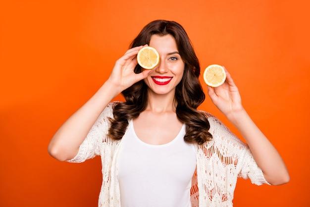 갈색 머리 쾌활한 긍정적 인 귀여운 좋은 매력적인 예쁜 여자가 장난스럽게 레몬의 절반 뒤에 그녀의 눈을 숨기고 이빨 웃고.