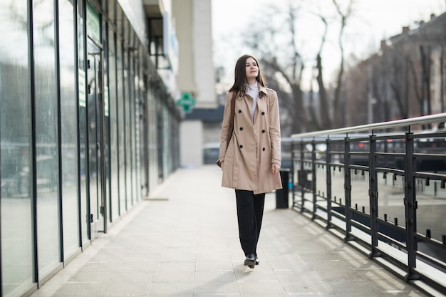 Modello femminile dai capelli castani che cammina per strada in abbigliamento casual