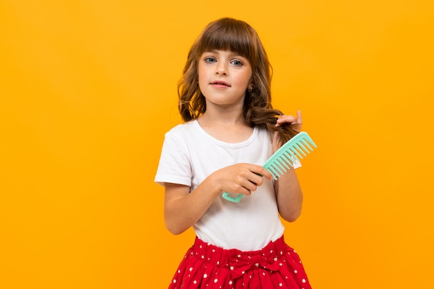 Brown-haired girl combing her hair on orange