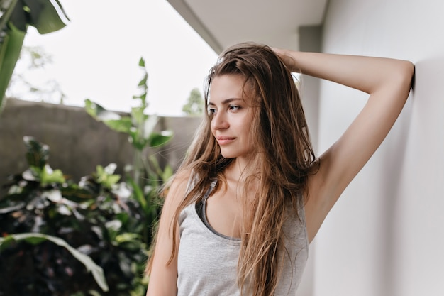 Brown-haired girl posing with dreamy face expression near white wall. pensive caucasian lady touching her long hair and looking away.
