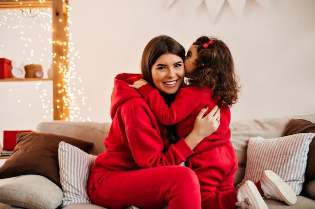 갈색 머리 아이가 거실에서 어머니를 키스. 작은 딸과 함께 시간을 보내는 젊은 여자의 실내 샷.