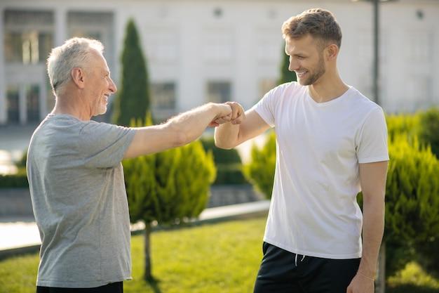 茶色の髪の男性と白髪の男性が拳に触れている