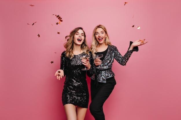 ワインを飲むショートドレスの茶色の髪の白人の女の子。シャンパンで何かを祝う壮大な女性の屋内写真。