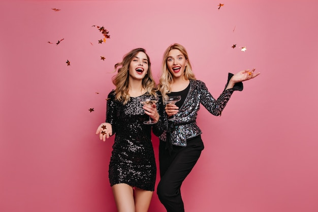 Brown-haired white girl in short dress drinking wine. indoor photo of spectacular ladies celebrating something with champagne.