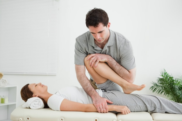 Brown-haired woman being stretched by a man in a room