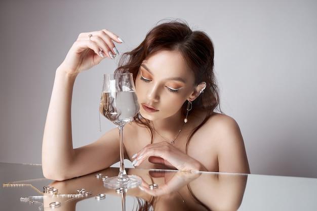 갈색 머리 여자 물 잔에 체인 펜던트를 삭제합니다.