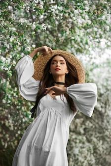 Шатенка в большой соломенной шляпе и белом платье позирует на фоне цветущих белых деревьев. романтичный вид, естественная красота, чистая кожа лица
