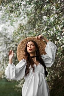 큰 밀짚모자를 쓰고 흰 드레스를 입은 갈색 머리의 여성이 만개한 흰 나무를 배경으로 포즈를 취하고 있다. 로맨틱한 외모, 자연미인, 깨끗한 얼굴 피부