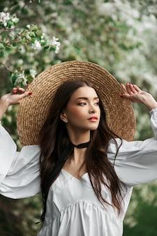 大きな麦わら帽子と白いドレスを着た茶色の髪の女性が、咲く白い木々を背景にポーズをとっています。ロマンチックな外観、自然の美しさ、きれいな顔の肌