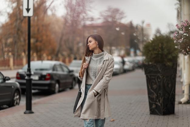 通りに沿ってポーズをとる革のバッグと春の服とスニーカーの茶色の髪の女性