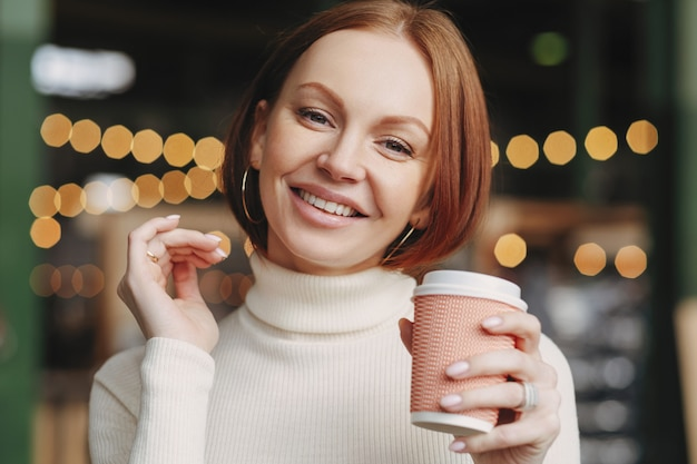 Brown haired woman with make up, toothy smile, dressed in white turtle neck sweater