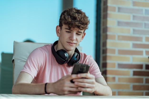ヘッドフォンとスマートフォンを手に茶色の髪の若い男