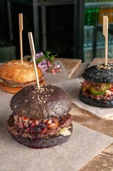 牛カツ、トマト、きゅうり、赤玉ねぎ、ワイルドベリーソースのブラウンハンバーガー。閉じる。背景には黒ハンバーガーと普通のハンバーガーがあります。