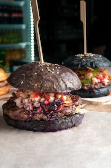 牛カツ、トマト、きゅうり、赤玉ねぎ、ワイルドベリーソースのブラウンハンバーガー。閉じる。背景には黒いハンバーガーがあります。