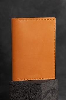 Коричневый кожаный кошелек ручной работы на бетонной поверхности