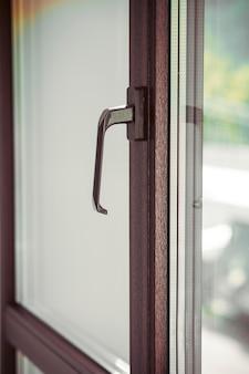 モダンなプラスチック窓の茶色のハンドル。クローズアップショット