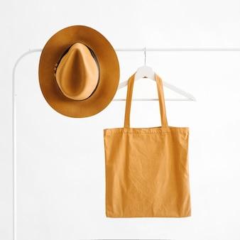 白い背景の上のハンガーに茶色の帽子とエコバッグ。最小限のコンセプト。