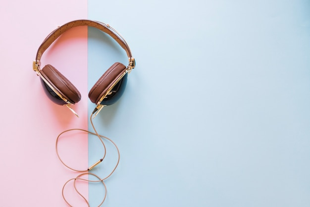 Brown headphones on pastel background