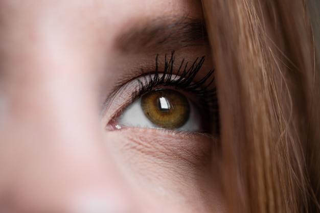Коричневый человеческий глаз крайний крупный план в технике низкой освещенности.
