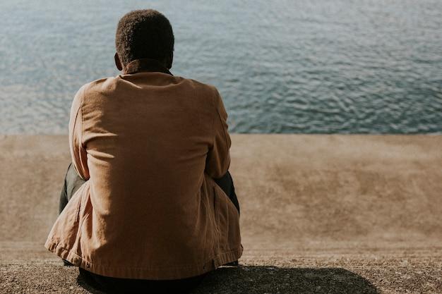 湖のそばの茶色のジャケットの背面図