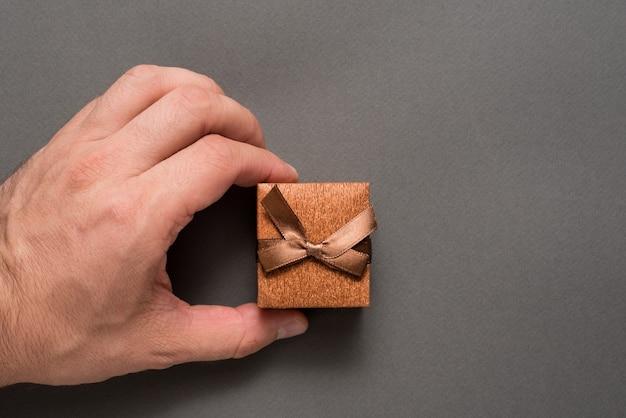 男の手で茶色の宝石箱。プレゼント。黒の背景