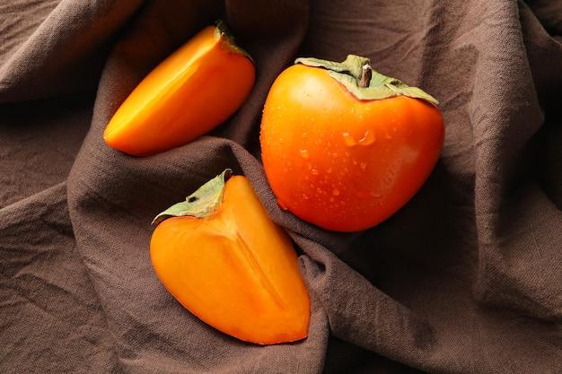 新鮮な熟した柿と茶色のキッチンタオル