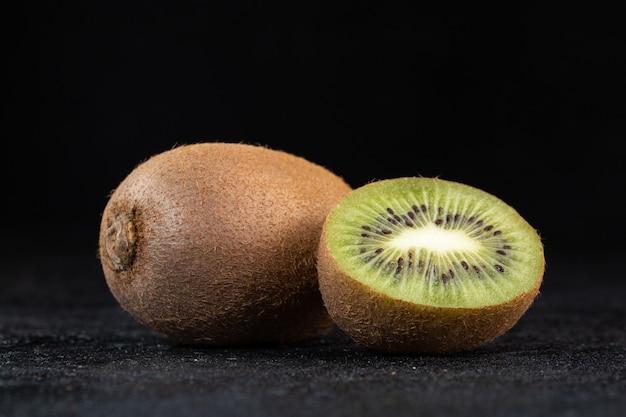 Brown kiwi fresh juicy mellow half cut isolated on dark