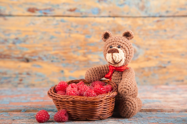 Brown knitted small bear with berry on an old wooden background. handmade, knitted toy. amigurumi