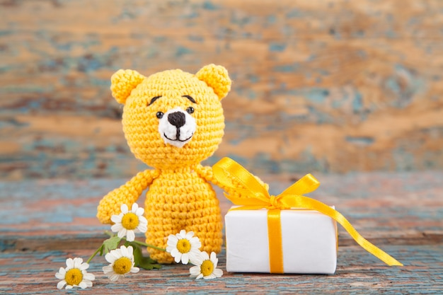 Brown knitted small bear with chamomile on an old wooden background. handmade, knitted toy. amigurumi