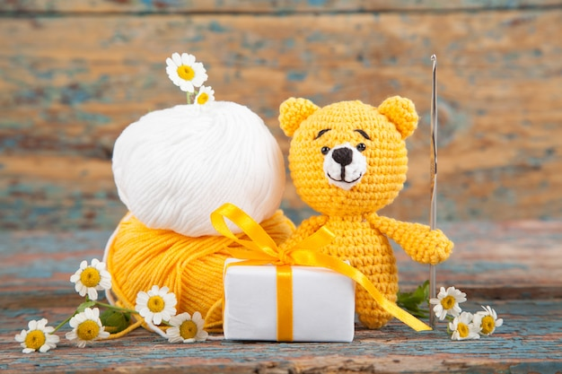 Brown knitted small bear with chamomile on an old wooden . handmade, knitted toy. amigurumi