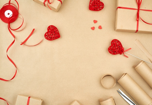 Brown kraft paper, packed gift bags and tied with a red ribbon, red heart background