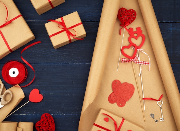 Brown kraft paper, packed gift bags and tied with a red ribbon, red heart, set of items for making gifts